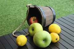 Still life of apples and lemons. Still life apples lemons rustic rough wooden grass town village nature vegeterian healthy food meal vitamins table yellow greeb stock images