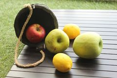 Still life of apples and lemons. Still life apples lemons rustic rough wooden grass town village nature vegeterian healthy food meal vitamins table yellow greeb stock photo