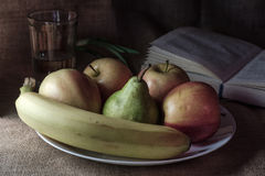 Still life with apples pear and banana. In the background is a glass with a book Stock Photo