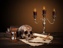 Still life art photography on human skull skeleton. With blank scroll and books. Concept of judge verdict stock photo