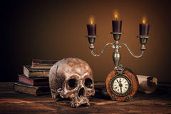 Still life art photography on human skull skeleton. With blank scroll and books. Concept of judge verdict royalty free stock photos