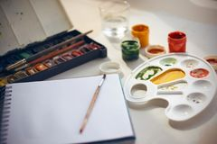 Still life with art supplies: paints, palette, sketchbook, brushes and water in a glass stock photography