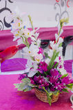 Still life of artificial flowers on the crimson tablecloths in the hall for the wedding celebrations Stock Photo