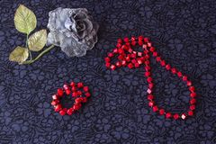 Still life of artificial rose with red beads and bracelet on textile background stock image