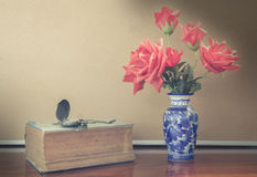 Still life artificial rose in vase with watch and book Royalty Free Stock Photography