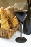 Still life assortment of bread with a glass of red wine and bott Stock Image