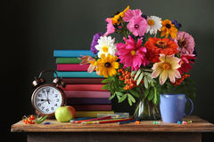 Still life with autumn bouquet, alarm clock and books. royalty free stock image