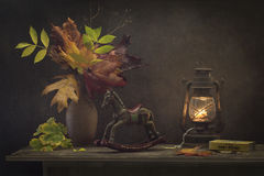 Still Life Autumn Evening. Still autumn evening with a decorative wooden horse, a clay jug with a bouquet of autumn leaves, orange, yellow, green, purple, with stock images