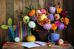 Still life with autumn flowers, books and pencils. Stock Photography