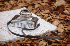 Still life in the autumn forest with camera and map Stock Photos