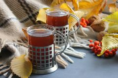 Autumn morning with a Cup of tea. A Cup of tea on a plaid background, surrounded by yellow leaves stock images