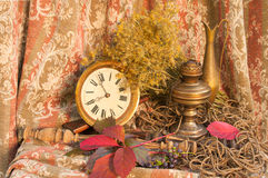 Still life. Autumnal still life with clock and oil lamp Royalty Free Stock Image