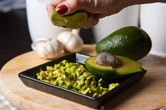 Still life of avocado fruit cut for a meal. Food photography: still life of green avocado fruit cut into pieces, being ready as an ingredient for a meal. Whole Stock Images
