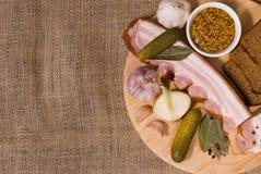Still Life: Bacon Appetizer on Round Wooden Board. Still Life: Bacon, Dijon Mustard, Bread, Garlic, Onion, Pickles on Round Wooden Board and Sackcloth Background Royalty Free Stock Photography