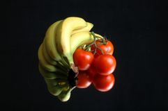 Still life banana and tomato. Studio still life banana and tomato with reflection on mirror and black background Royalty Free Stock Images