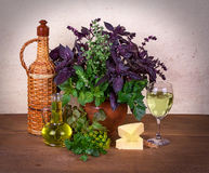 Still life with basil, celery, dill, marjoram, parsley, lettuce; cheese and wine Royalty Free Stock Image