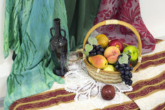 Still life with basket , artificial fruit, old bottle and glass Stock Images