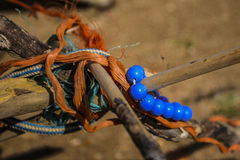 Still life. On the beach made of sticks tied with orange rope and plastic beads necklace blue Royalty Free Stock Photography