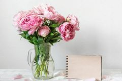 Still life with a beautiful bouquet of pink peony flowers and blank paper notebook. mock up. holiday background royalty free stock image