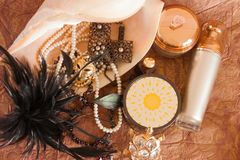 Still life of beautiful jewelry in a large shell, luxury skin care products and black feathers. stock image