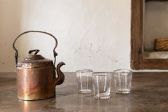 Vintage brass tea pot with empty glasses Stock Photography