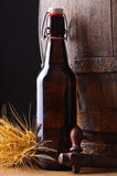 Still life with beer bottle. Wheat and wooden barrel in background Royalty Free Stock Image
