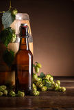 Still life with beer. Bottle, hops and wooden barrel Stock Images