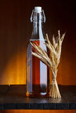 Still-life of beer bottle with wheat bunch Stock Photography