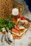 Still Life With Beer And Fish. Glass of beer, fish, bread and greenery royalty free stock image
