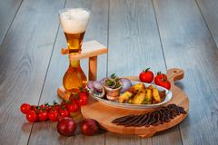 Still life with beer, herring, cured meat, country-style potatoes royalty free stock photos