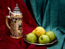 Still Life with a beer mug. Green apples and yellow limonami Royalty Free Stock Photography