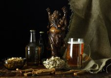 Still life with a beer in a retro style. Still life in retro style with a mug of beer, peanuts, breadcrumbs and antique Chinese sculpture of a drunkard Stock Photography
