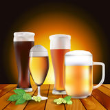 Still life with beers and hops on wooden table Royalty Free Stock Photo
