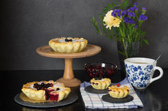 Still life with berry pies and cup of tea Stock Photography