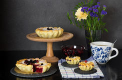 Still life with berry pies and cup of tea Stock Image