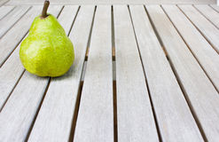 Still life with a big green pear on a white wooden table. Royalty Free Stock Photography