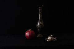 Still life on black. Still-life on a black background, an old vase and pomegranate royalty free stock image