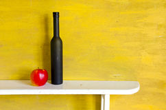 Still-life with black bottle and apple Royalty Free Stock Photo