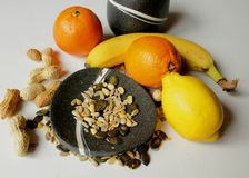 Still life - black bowls with fresh fruit and various seeds. Still life - black bowls with banana, lemon, two oranges, peanuts and pumpkin and sunflower seeds stock photos