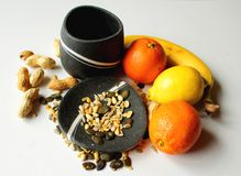 Still life - black bowls with fresh fruit and seeds. Still life - black bowls with banana, lemon, two oranges, peanuts and pumpkin and sunflower seeds stock image