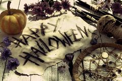 Still life with black candles, pumpkin, happy halloween text and dream catcher on planks stock images