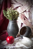 Still Life with a black jug and a red apple. On the table Royalty Free Stock Photo