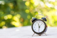 Alarm clock on a light surface on a natural background. Summer concept stock photography