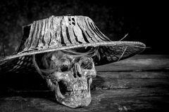 Still life black and white human skulls on wood. Still life black and white photography with human skulls on wood table Royalty Free Stock Images