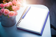 Still life of blank note book and pen with flower. Vintage filtered with scratch added. stock photography