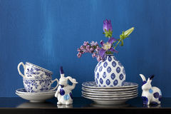 Still life with blue and white dishes and flowers in a little va Royalty Free Stock Image