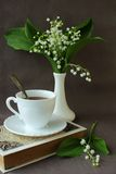 Still life with a book, a cup of coffee and a sprig of lily of the valley Royalty Free Stock Image