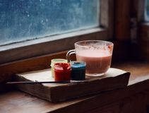 Still life from a book, Cup and paints. On an old wooden windowsill royalty free stock image