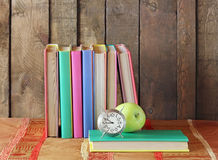 Still life with books, apple and an alarm clock. Back to school Royalty Free Stock Image