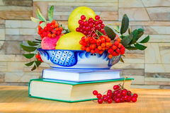 Still life: books and fruit and berries in a beautiful vase.